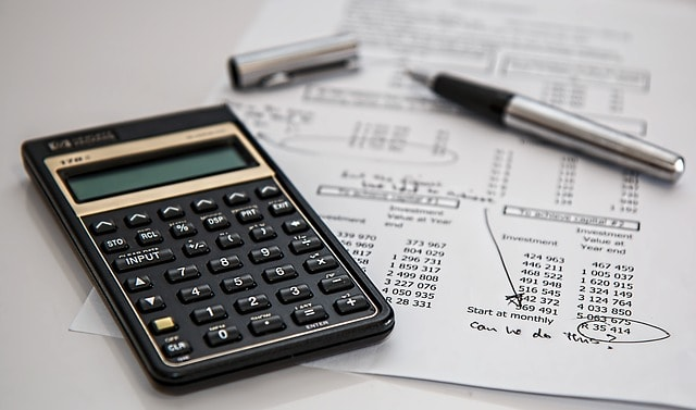 A calculator and pen are placed on top of a paper filled with budgeting numbers.